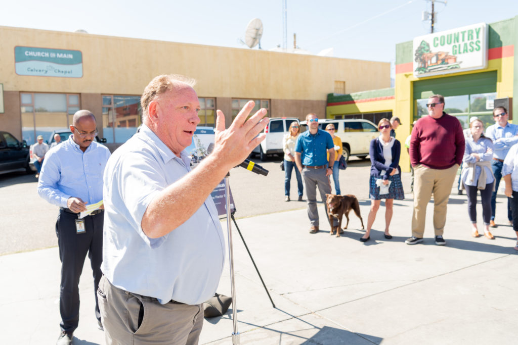 man speaking in microphone at outdoor public event.