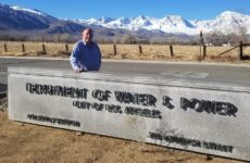 man standing behind Los Angeles Department of Water and Power sign with snow capped mountains.