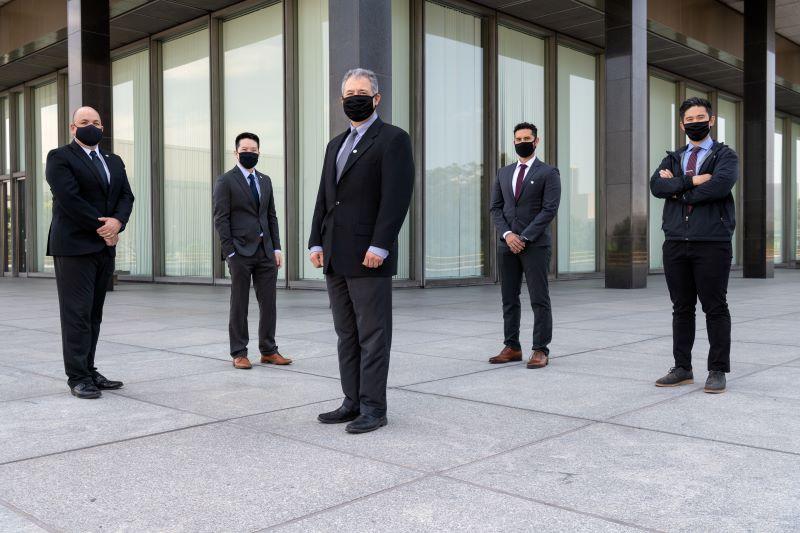 photo of men standing in front of DWP building